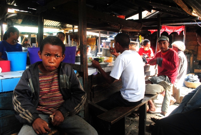Street kid eating chicken bone