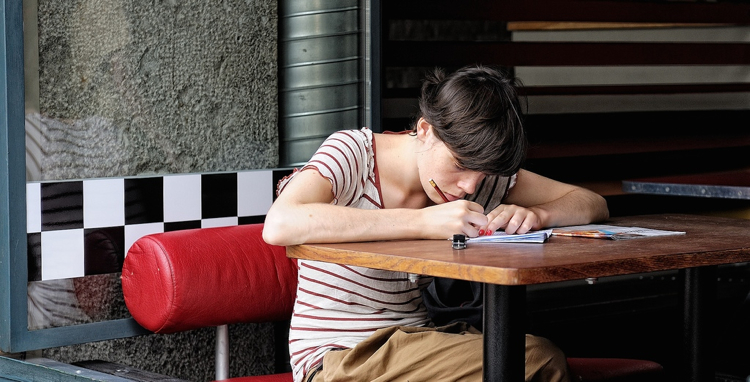 Girl writing in a cafe