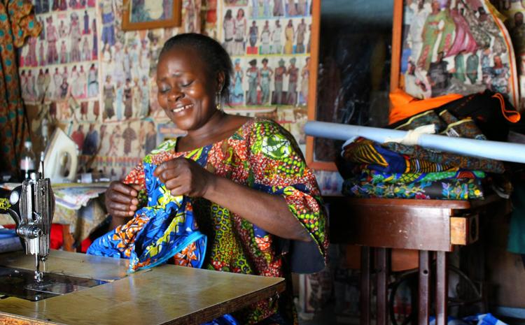 Seamstress in Cameroon sewing a muumuu